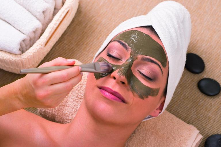 Frau wird mit frisch angerührter Algenmaske eingestriche